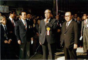 渡辺大臣の隣で挨拶する 荒牧清八理事長